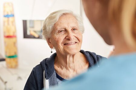 Satisfied senior woman in rehab together with physical therapist