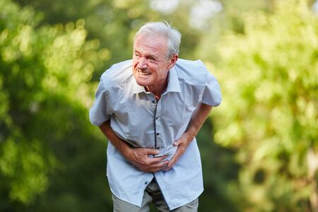 Old man with stomach ache holding his stomach in nature