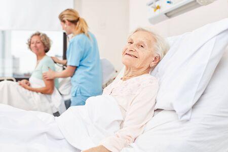 Happy senior citizen in hospital bed in nursing home or hospital