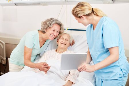 Nurse with tablet computer on bed of a senior woman with daughter