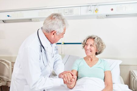 Doctor looks after a satisfied patient and holds her hands thoughtfully