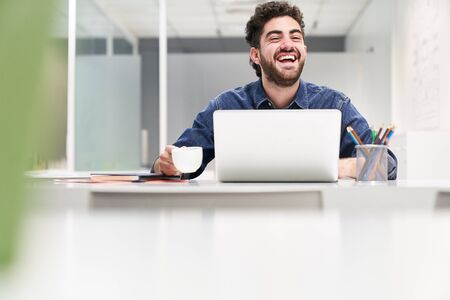 Laughing student or entrepreneur at laptop computer in start-up business office Stock Photo