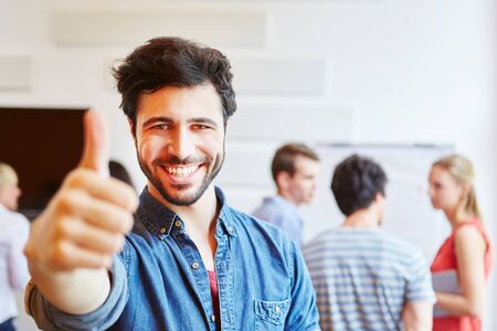 Smiling student in a start-up company holds his thumb up