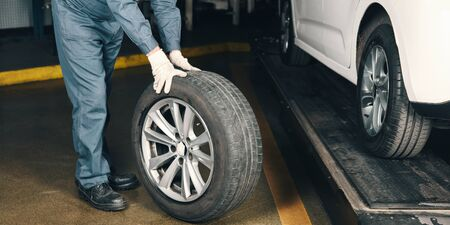 Mechatronics engineer changing tires in car in car workshop