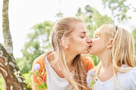 Mother lovingly gives her daughter a kiss in the garden in summer