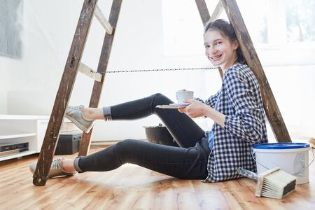 Young do-it-yourself lady renovating or moving makes a coffee break 版權商用圖片 - 141171633
