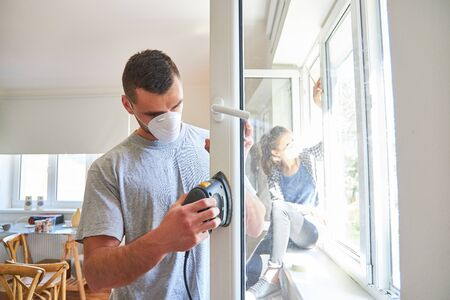 Young man as a home improvement while sanding and working up from a window frame