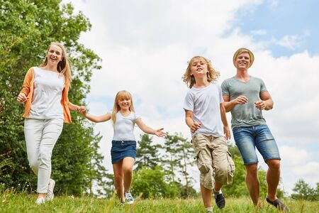 Active family and children run happily in summer on a meadow