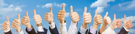 Business group with thumbs up under the sky