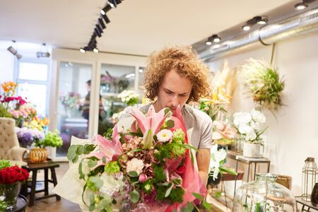 Young florist ties a bouquet of flowers as a gift in the flower shop