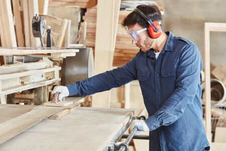 Carpenter grinds wood on a belt grinding machine in the joinery Stok Fotoğraf