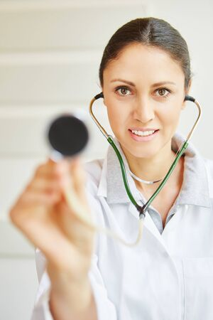 Woman as doctor with stethoscope listening in on consultation Banco de Imagens