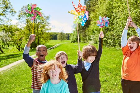 Group of kids with pinwheel happily celebrates a kid's birthday in the summer in the park