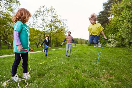 Active children play jump rope in the park together in the summer in a meadow