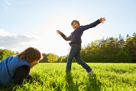 Boy is kidding around while dancing with a girl on a meadow in the sunshine