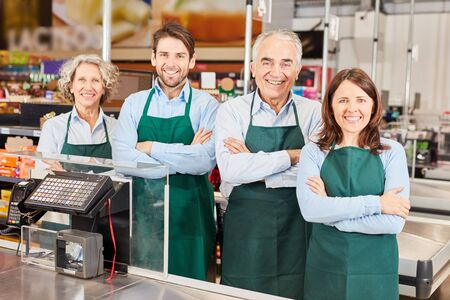 Happy group of sales people with market leader at the cash desk in the supermarket