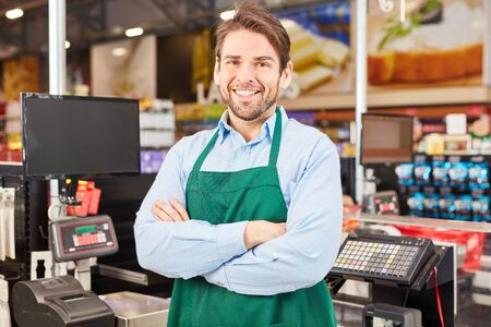 Smiling man as a satisfied salesman or cashier at the supermarket checkout