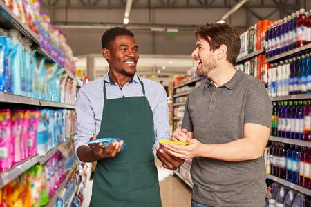Friendly African seller in the supermarket at a customer consultation Stock Photo