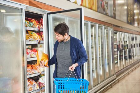 Customer in the supermarket is standing at frozen food in the refrigerator shelf and looks at a pack of French fries Reklamní fotografie