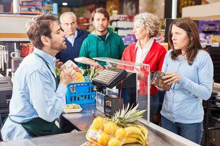 Customer at the supermarket cashier has too little money in the wallet for shopping Banque d'images