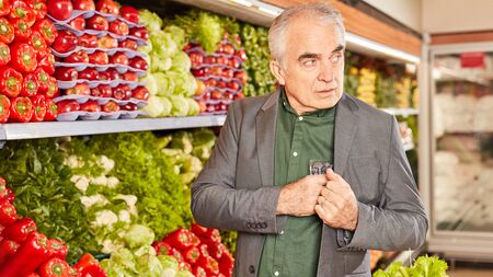 Senior as a shoplifter in the vegetable department secretly hides food