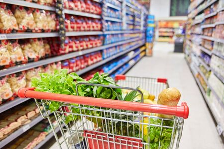 Shopping cart with many foods in a corridor in the supermarket Banco de Imagens