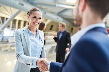 Business people arrange cooperation by handshake in the airport terminal