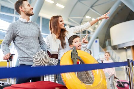 Happy family in the airport terminal is happy about the punctual departure on vacation Reklamní fotografie