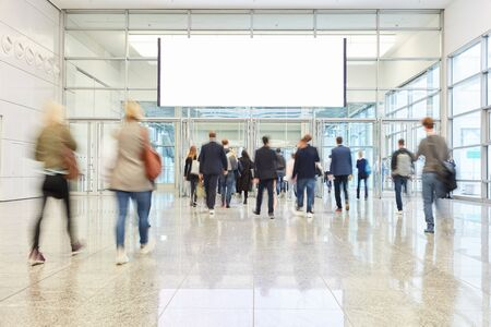 Many anonymous people under blank white advertising poster on a trade fair Foto de archivo