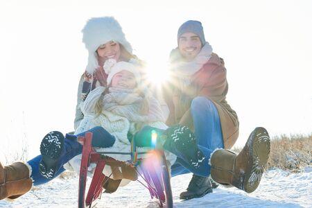 Famille heureuse en traîneau et en traîneau dans la neige en hiver Banque d'images