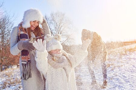 Family playing in the snow in winter makes a snowball fight