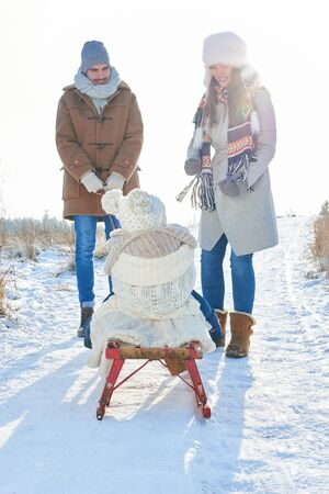 Parents pull child on sled in winter while walking