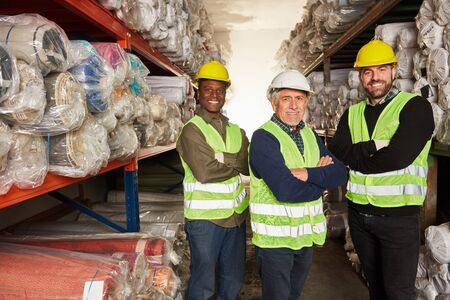 Successful logistics worker team in carpet warehouse at the shipping center
