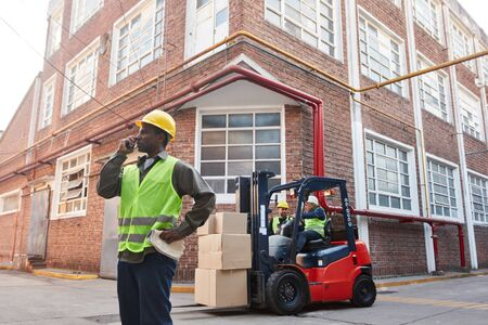 Logistics worker with forklift and cargo in front of the warehouse of a freight forwarder Banque d'images