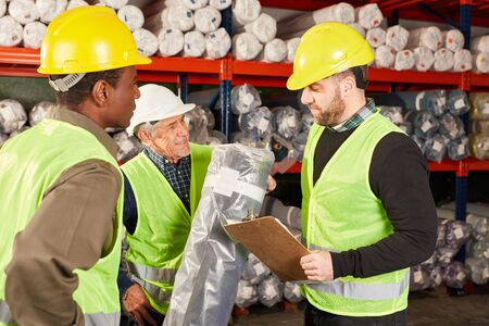 Warehouse worker team inspects a delivery in the carpet warehouse by mail order Banque d'images