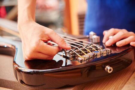 Hand of guitar maker works on electric guitar with an Allen key Foto de archivo