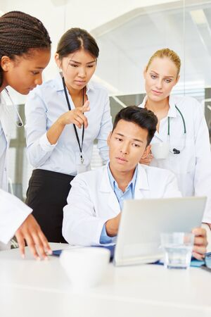 Doctor and hospital staff work together with tablet computer