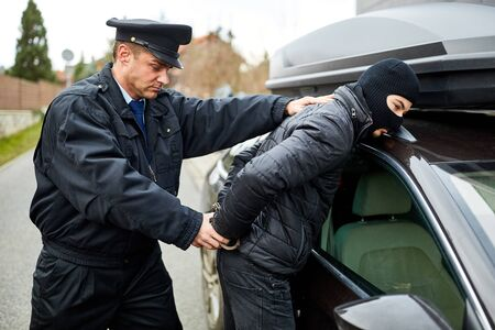 Police officer arrests car thief in the act and handcuffs him on arrest