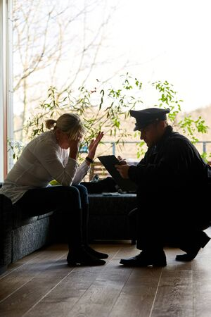 Weeping woman talks to policeman after breaking into the house Stock fotó