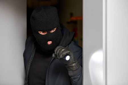 Masked burglar in the house at burglary with a flashlight
