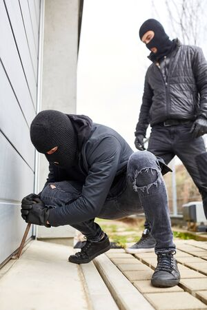 Burglars pry open the gate of a garage or warehouse with a crowbar