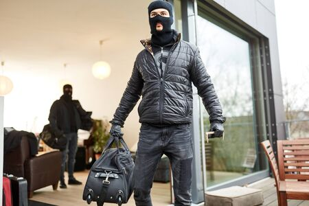Burglars flee with bags of loot from a house