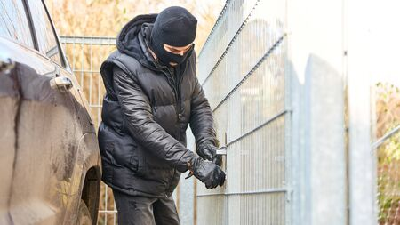 Burglar crackles on door of a gate at the fence Banque d'images