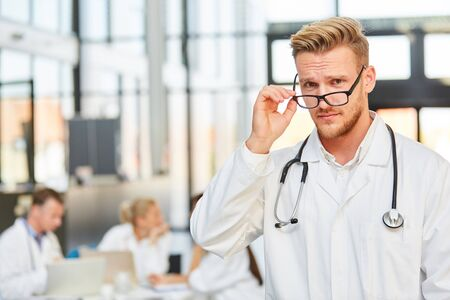 Arrogant man with glasses as a medical assistant in training at the hospital meeting Stock fotó