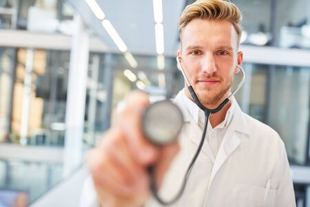 Young man as an internist with stethoscope in education or medical school