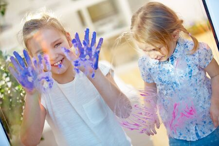 Children draw fingerprints on a glass pane with their finger paints and hands