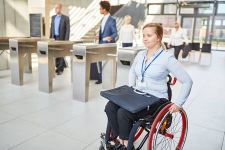 Businesswoman in a wheelchair accessible past the security gate in the office Stock Photo