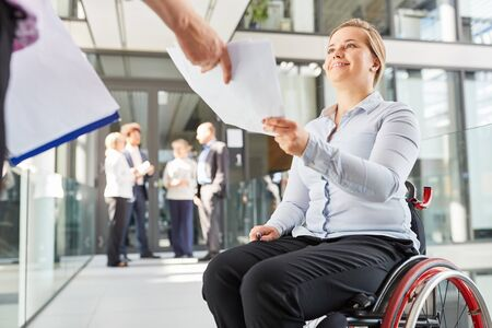 Smiling businesswoman in a wheelchair gets documents from colleagues in the office