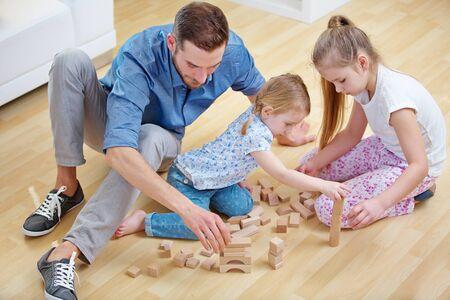 Une famille avec un père et deux enfants joue avec des blocs de construction à la maison