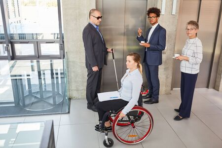 Multicultural business team with disabled colleagues at the elevator for inclusion